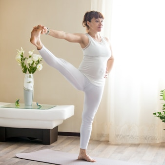Беременная женщина делает расширенную руку на большую ногу йоги позирует дома