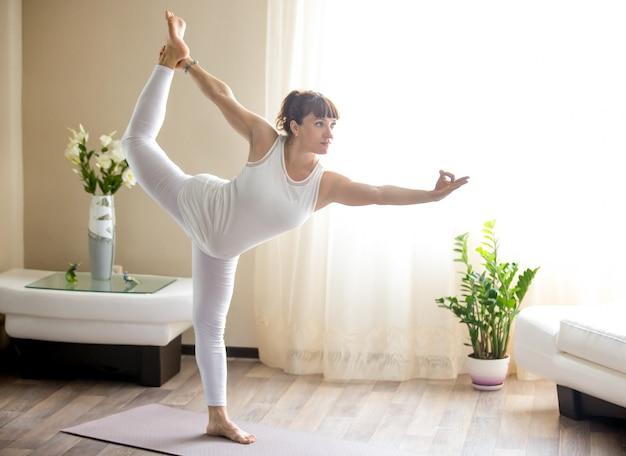 Беременная женщина, делающая лорда танцевальной йоги, ставит дома