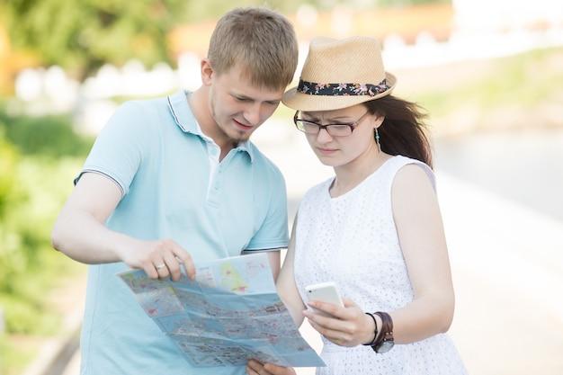 地図や電話で旅行するカップルが旅行で迷子になった