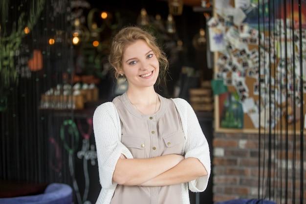 彼女自身のコーヒーショップでポーズをとっている幸せなビジネス女性を笑顔