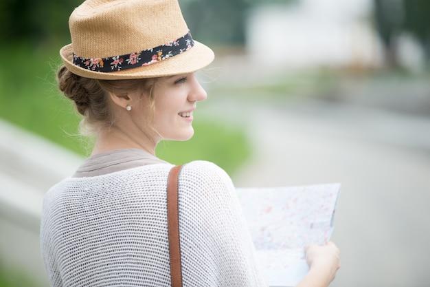 地図を保持している麦わら帽子の若い旅行者の女性。背面図