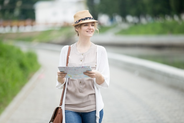 若い旅行者の女性は、旅行の地図で歩くストロー帽子で
