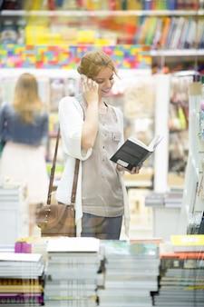 Портрет молодой женщины счастливы выборе книги в книжном магазине