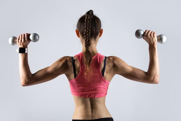 体重を使って運動するスポーティーな女性。背面図