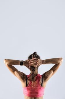 Спортивная девушка позирует с руками за головой. вид сзади
