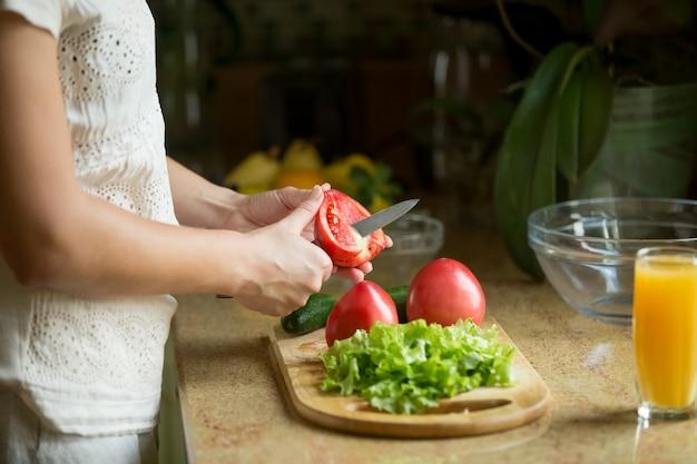 手はトマトを切る、ボード上にサラダ
