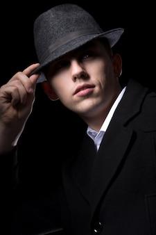 彼の帽子の後ろに隠れている男