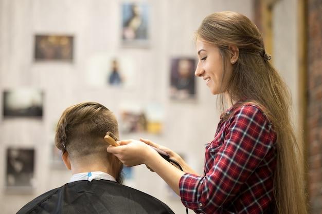 Молодая женщина-парикмахерка работает