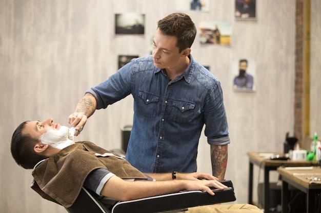 理髪店でひげ剃りをするクライアント