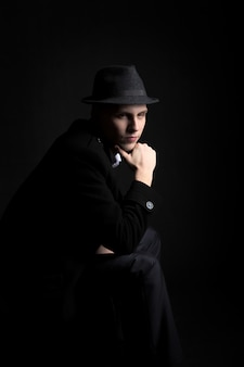 暗闇の中の帽子を着た思慮深い若い男