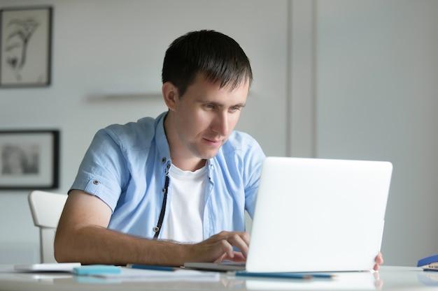 Портрет молодой человек, работающих на стол с ноутбуком