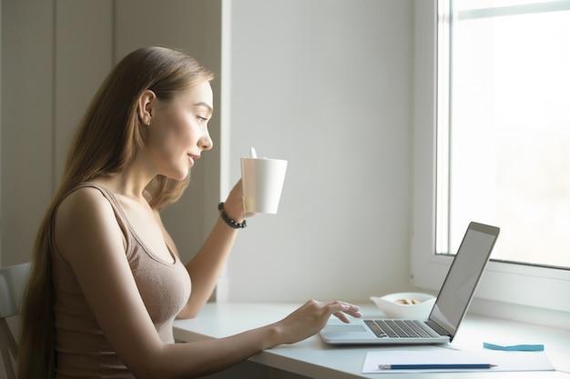 窓の上にラップトップを持つ女性のプロフィールの肖像