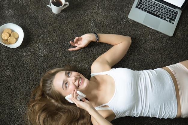 彼女の電話で話す、嘘をついた女性のトップビューの肖像画