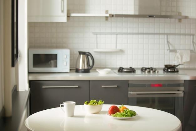 モダンキッチン、白いテーブル、マグカップ、グリーンサラダ