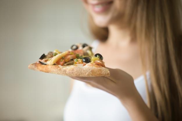彼女の手にピザのスライスを握っている笑顔の女の子