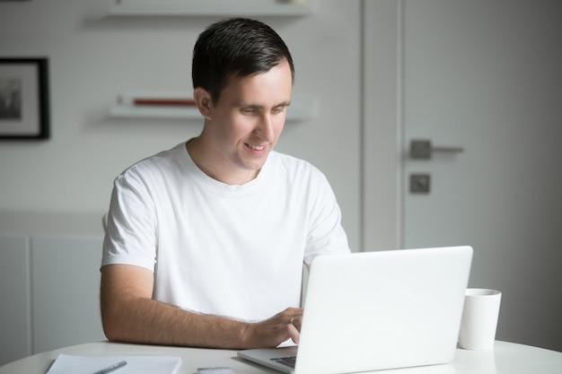 Молодой человек, сидя на белый стол, работающий с ноутбуком