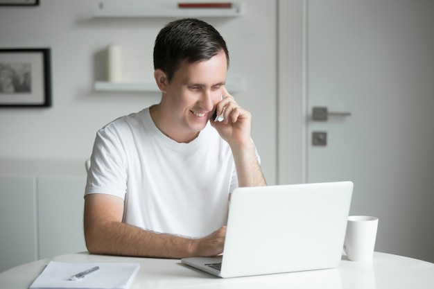 Молодой человек, разговариваете по телефону на белом столе, работающих на ноутбуке