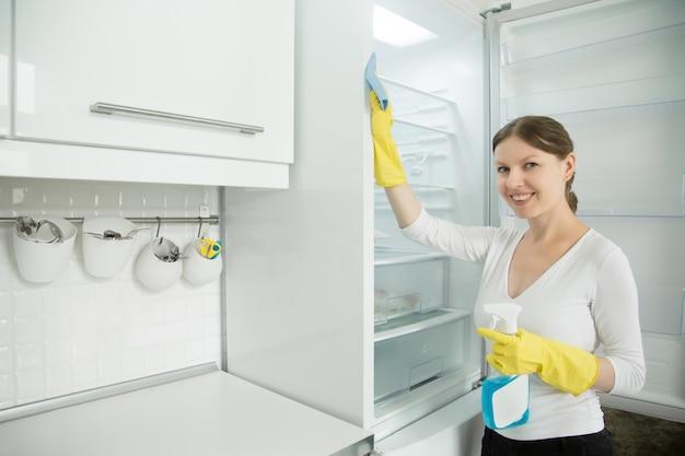 冷蔵庫を掃除するゴム手袋を着ている若い笑顔の女性