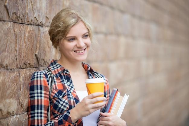 Портрет студенческой девушки против кирпичной стены