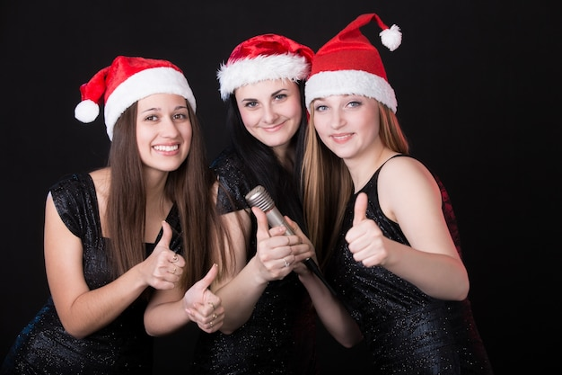 Три привлекательные девушки санта с микрофоном, показывающие