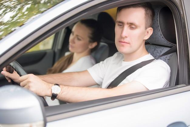 Молодой мужчина-водитель смотрит в зеркало заднего вида
