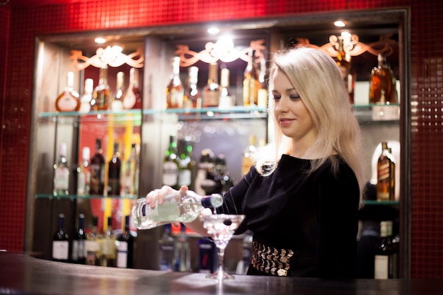 Девушка-бармен, служащая мартини
