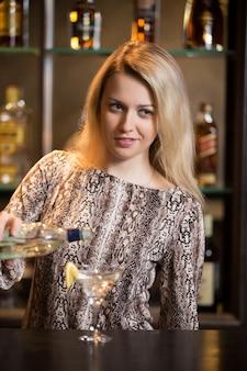 Блондинка бармен делает коктейль