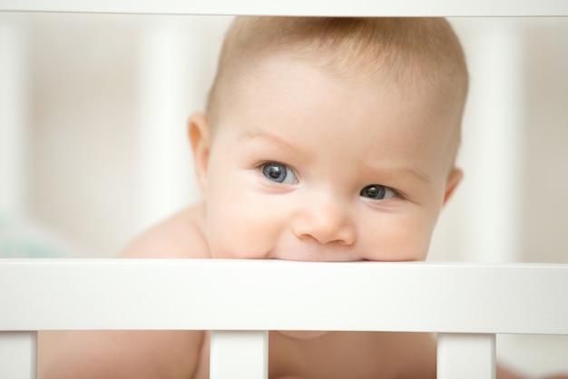 彼の木製ベッドのボードを噛む愛らしい赤ちゃん