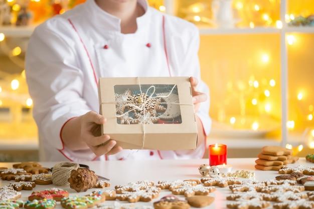 ジンジャーブレッドクッキーの入った箱を示す菓子屋の手
