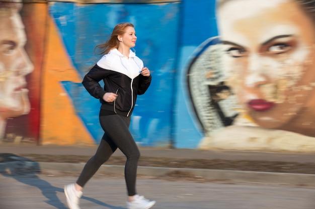 落書きの壁の横に朝のジョギング