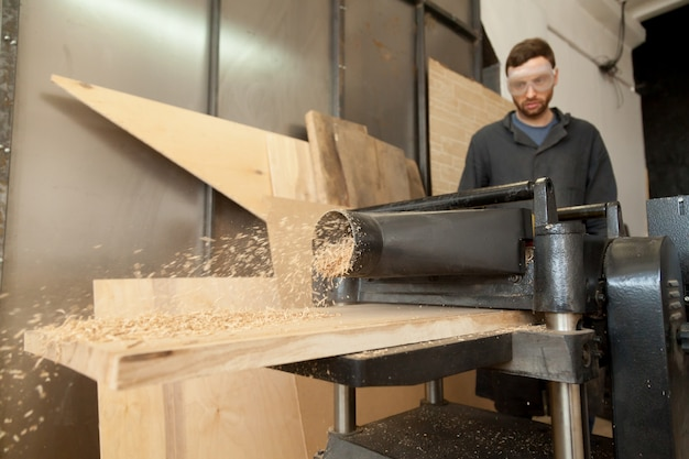 木材の厚板で固定パワープレーナーで作業するカーペンターのジョイナー