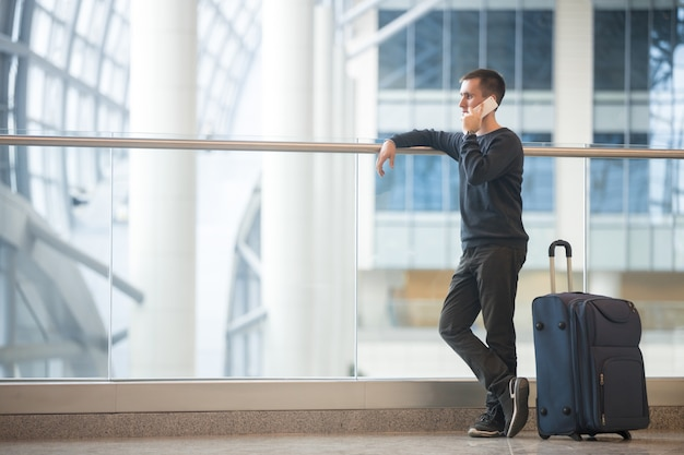 空港でスマートフォンで話す若い旅行者