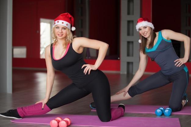 Две красивые девушки в шляпах санта-клауса тренируются на матах в фитнес-центре