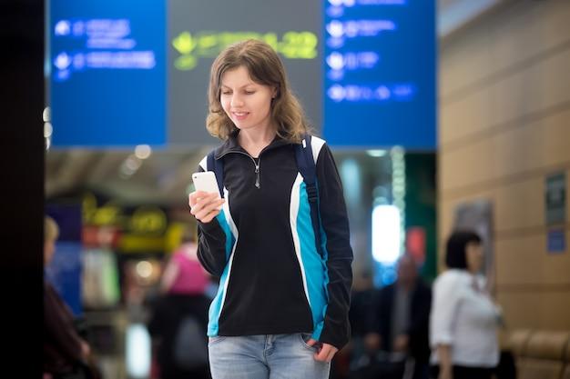Девушка с мобильным телефоном в аэропорту