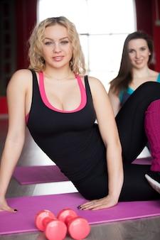 女性はフィットネスクラスのマットでフィットネストレーニングをします