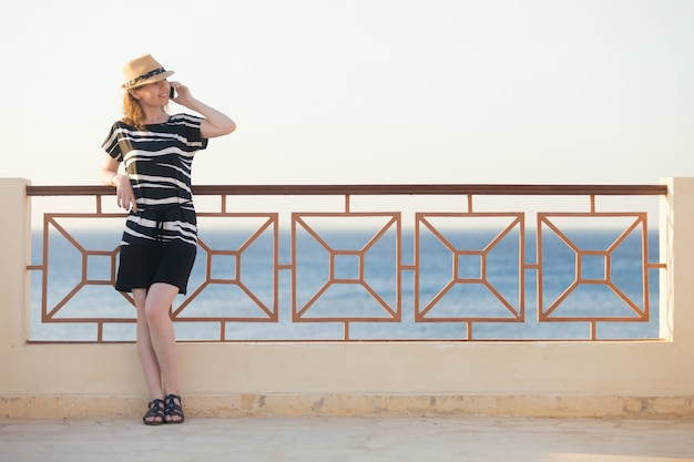 Молодая женщина на телефоне на морском курорте