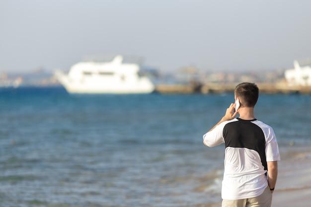 Молодой человек разговаривает по мобильному телефону в море