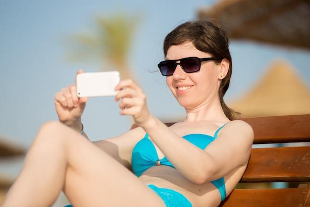 女性、木製の椅子に携帯電話で写真を撮る