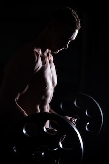 Мускулистый мужчина делает тяжелую атлетику в фитнес-центре