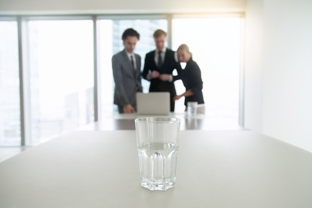 オフィスの机の上の水のガラスのクローズアップ