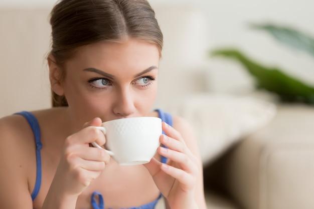 Молодая женщина, наслаждаясь горячим свежесваренным кофе