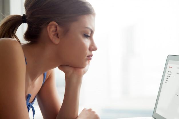 ノートパソコンの画面に電子メールの手紙を読む女