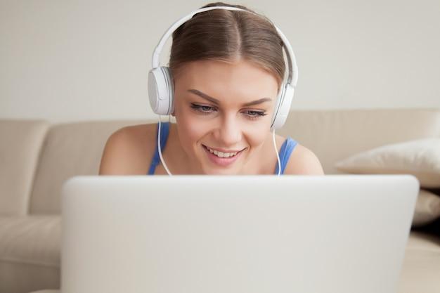 ラップトップ、ヘッドショットを使用してヘッドフォンを着ている若い女性の笑みを浮かべてください。