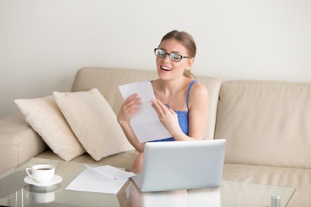 良い結果の手紙を楽しんで興奮している女性は、仕事を得て、試験に合格しました