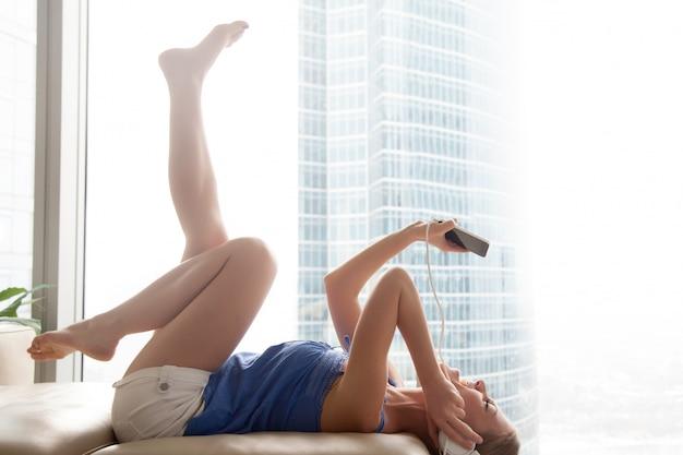 若い女性がソファーに横になっているヘッドフォンでスマートフォンの音楽を聴く