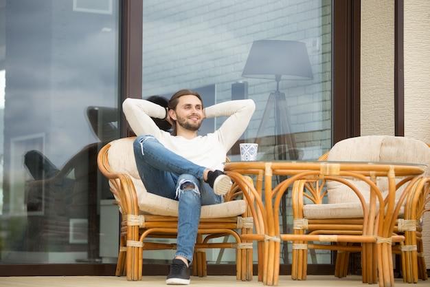 屋外テラスに座って楽しい朝を楽しんでいるリラックスした男の笑みを浮かべてください。