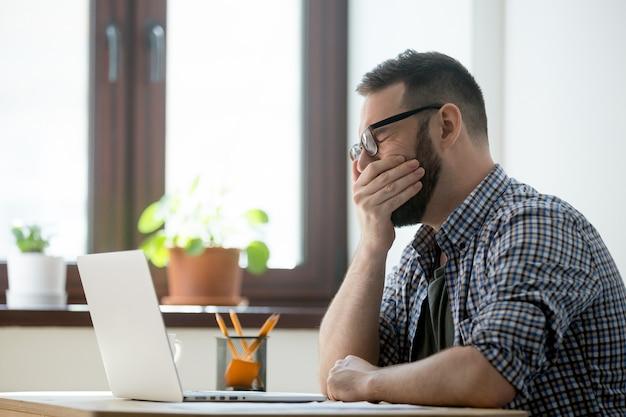 オフィスでの仕事であくびメガネで疲れて眠そうなマネージャー