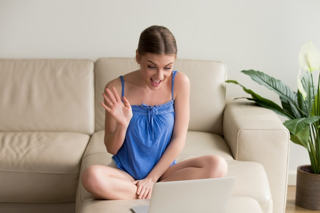 ラップトップ上の距離ビデオ通話を作る若い女性の笑みを浮かべてください。