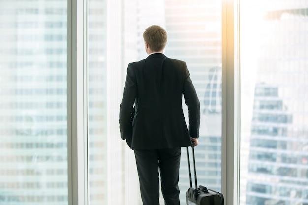 窓の近くのスーツケースと一緒に立っている実業家