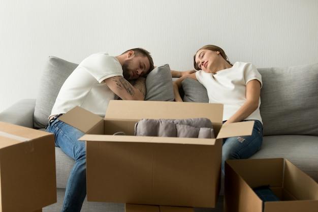Усталая молодая пара отдыхает на диване и переезжает в новый дом